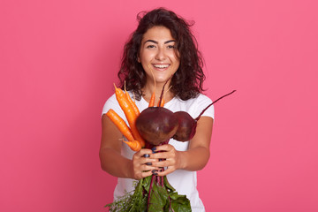 Image of energetic attractive curly haired cute brunette looking directly at camera, holding beet and carrots in hands, being in high spirits, sticking to healthy lifestyle. Vegetarian concept.