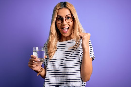 Young blonde healthy woman wearing glasses drinking glass of water over purple background screaming proud and celebrating victory and success very excited, cheering emotion