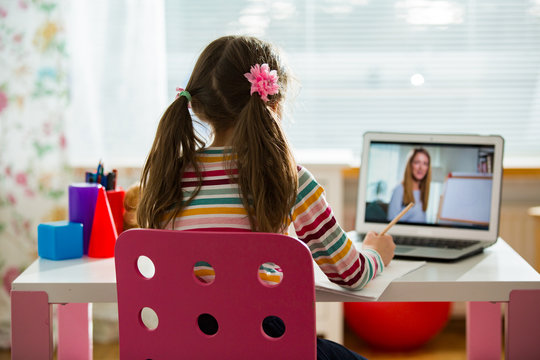 Young female distance teacher having video conference call with pupil using webcam. Online education and e-learning concept. Home quarantine distance learning and working from home.