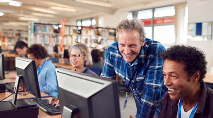 Teacher With Group Of Mature Adult Students In Class Working At Computers In College Library Fotobehang