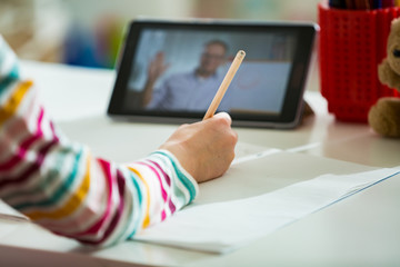 Primary school student having video conference call with teacher using webcam. Online education and e-learning concept. Home quarantine distance learning and working from home. Empty screen.