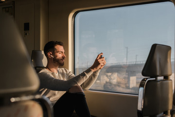 Concentrated youthful male passenger photographing on cellphone through window while sitting in train