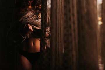 Crop seductive female in black lingerie and sweater showing tummy while standing in dark in room