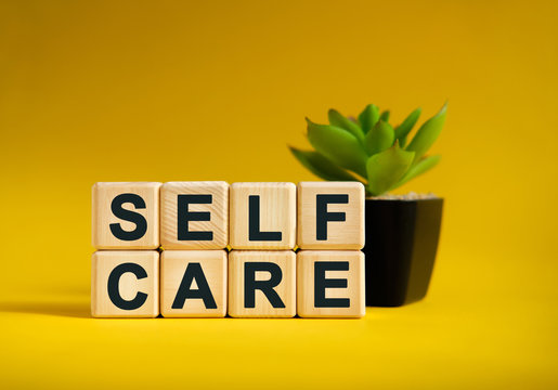 SELF CARE - text on wooden cubes, green plant in black pot on a yellow background