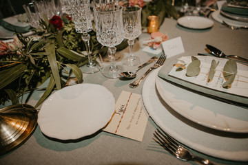 Various dishware and name card arranged with flowers and elegant glassware on table for wedding reception
