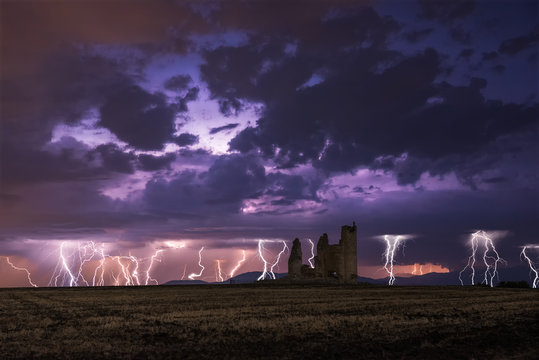 Amazing scenery of lightning storm on colorful cloudy sky over ruined old castle at night