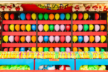 balloons and prizes at a dart throwing game booth at a carnival, fair, or amusement park