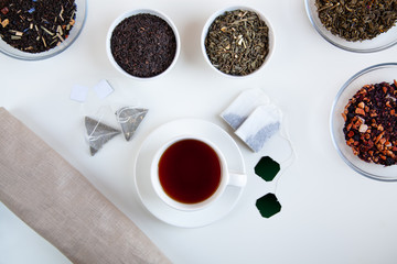 Assortment of dry tea in round bowls on a white background.