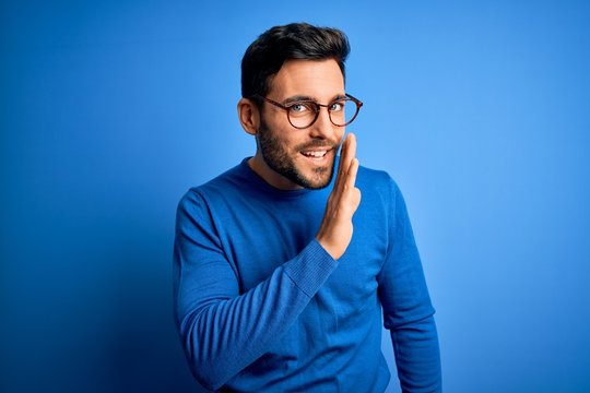 Young handsome man with beard wearing casual sweater and glasses over blue background hand on mouth telling secret rumor, whispering malicious talk conversation