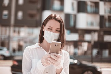 Young woman using smart phone in the city wearing face mask  and gloves protection for virus coronavirus covid 19