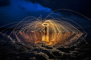 Man With Wire Wool On Shore Against Sky