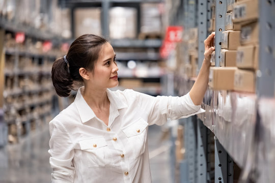 Smart Asian young woman happy to work in store warehouse. Girl standing and checking quality and quantity of inventory stock on shelf by model name and serial number it show on packaging of goods.