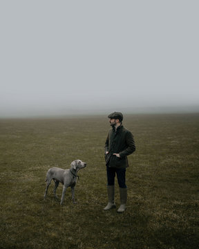 Man with dog in a foggy field