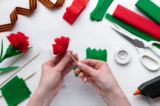 How to make carnation flower at home. Hands making red carnation to Victory Day 9 May. Step by step photo instruction. Step 11. Attach flower to stem of wooden stick. Children DIY art project.
