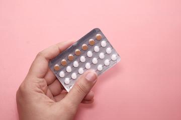 Obraz women hand holding birth control pills on pink. - fototapety do salonu