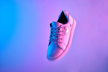 Trendy white teenage sneaker flying in trendy neon light. Levitation Shoe in red, blue light. Creative minimalism. Fototapete