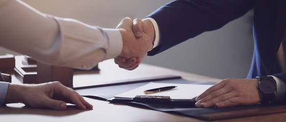 Male lawyer shaking hands with client in office, closeup. Banner design