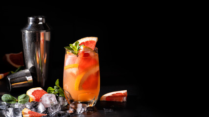 Grapefruit cocktail with mint and ice. Cold summer citrus fresh beverage and shaker on dark background