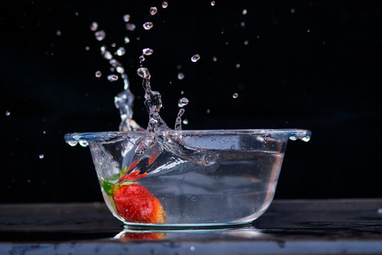 Transparent bowl with water splash and strawberry