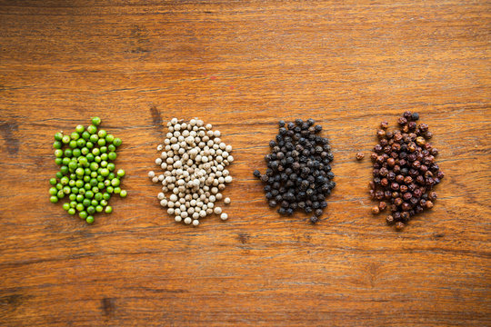 Red, white, black and green pepper corns over a wood surface.