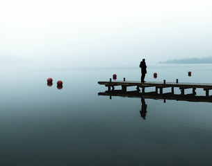 Silhouette Man Standing On Pier Over Sea Against Sky During Foggy Weather