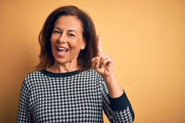 Wall Mural - Middle age beautiful woman wearing casual sweater over isolated yellow background pointing finger up with successful idea. Exited and happy. Number one.
