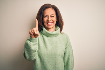 Wall Mural - Middle age beautiful woman wearing casual turtleneck sweater over isolated white background showing and pointing up with finger number one while smiling confident and happy.