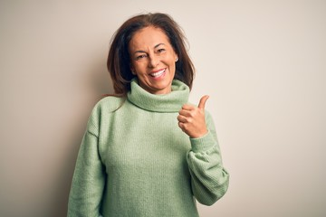 Wall Mural - Middle age beautiful woman wearing casual turtleneck sweater over isolated white background smiling with happy face looking and pointing to the side with thumb up.
