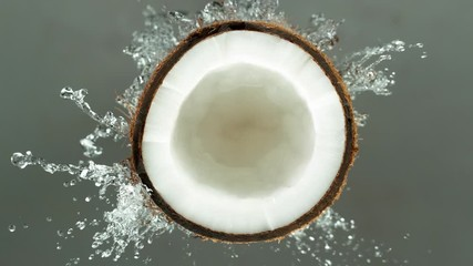 Wall Mural - Super Slow Motion Shot of Water Splashing on Coconut isolated on grey background.