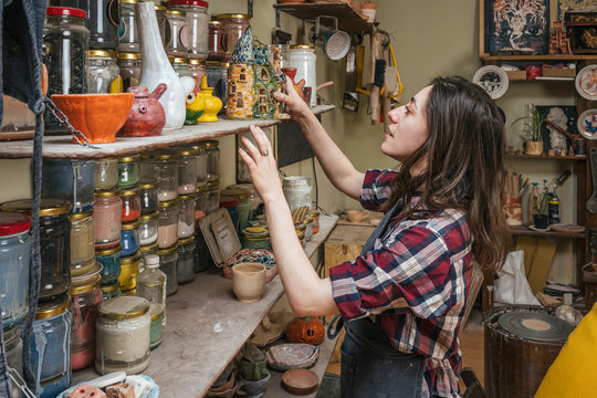 Potter at a shelf with products in workshop