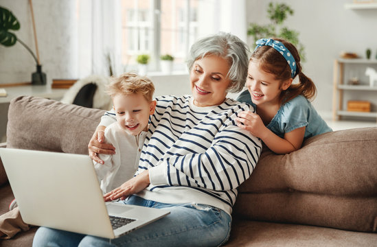 Happy aged woman with grandchildren using laptop at home