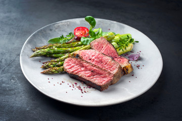 Tuinposter Steakhouse Barbecue dry aged wagyu entrecote beef steak with lettuce and green asparagus as closeup on a modern design plate