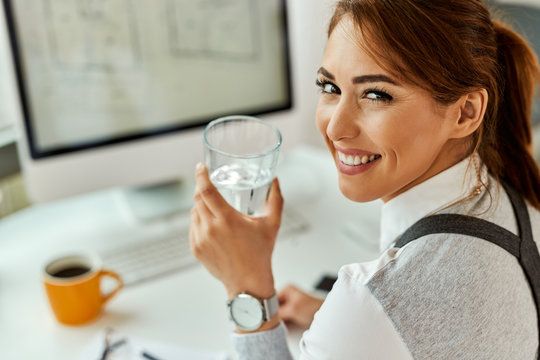 Happy businesswoman having a glass of water while working in the office.