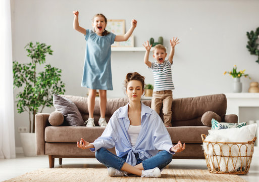 Tranquil young mother practicing yoga to stay calm with mischievous kids at home.