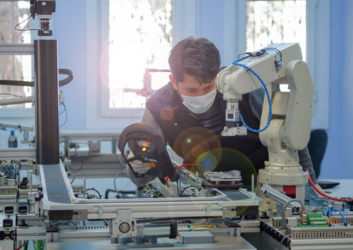 Man with surgical mask on face against COVID-19 ( Coronavirusis ) programming robot arm with control panel which is integrated on smart factory production line. industry 4.0 automation line.