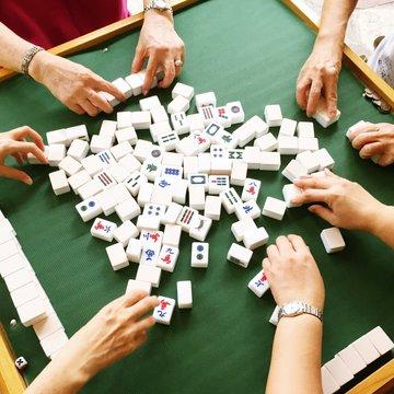 High Angle View Of People Playing With Mahjong Tiles On Table
