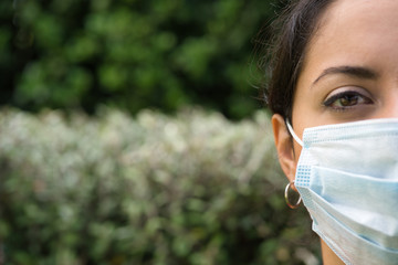 Face of a woman wearing face mask looking sad in outdoor background. Covid-19 concept