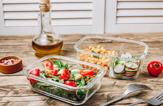 Healthy meal prep containers with chickpeas and spring salad with cucumbers, radish and chives and containers with caprese salad with arugula. Healthy lunch in glass containers. Zero waste concept.