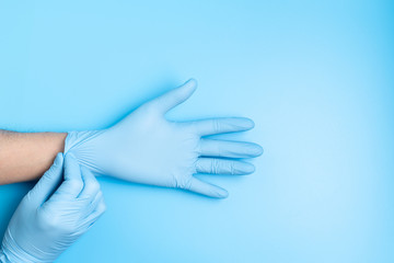 Surgeon putting medical gloves on isolated on blue background