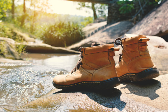 Close-up Of Shoes On Rock By River