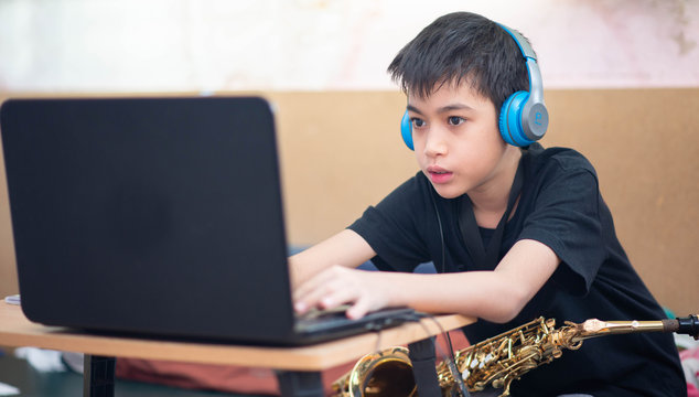 Little Asian boy study saxophone instument music online at home