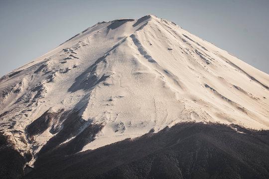 富士山。冠雪した富士を望遠レンズで。表面に残った雪と朝日が当たった部分の立体感。