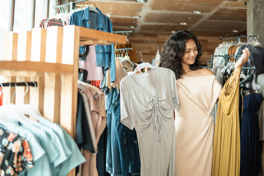 beautiful asian woman looking at some clothes in the fashion store. shopping concept