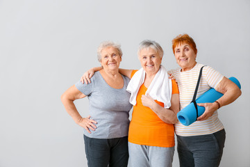 Happy elderly women with yoga mat on light background