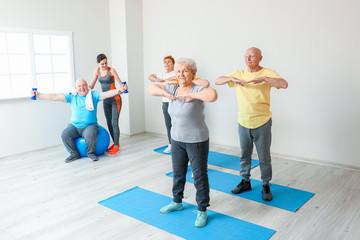 Elderly people exercising in gym