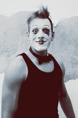 Portrait Of Young Man With Clown Face Paint Standing Against Weathered Wall