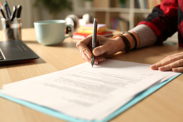 Student girl hand signing contract at night