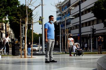 People stand still in Tel Aviv as a two-minute siren marking the annual Israeli Holocaust Remembrance Day is heard amid the coronavirus disease (COVID-19) restrictions around the country