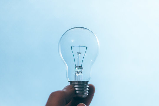 Cropped Hand Of Person Holding Light Bulb Against Blue Background