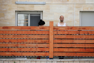 People stand still in their home in Ashkelon as a two-minute siren marking the annual Israeli Holocaust Remembrance Day is heard amid the coronavirus disease (COVID-19) restrictions around the country
